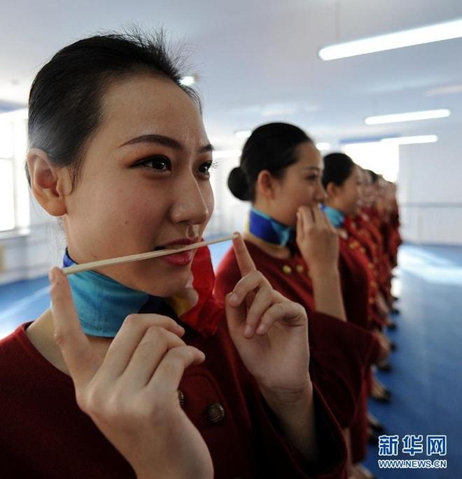 Ben trong lo luyen tiep vien hang khong Trung Quoc hinh anh 2 Các nữ sinh tập cười tươi khi phục vụ khách.