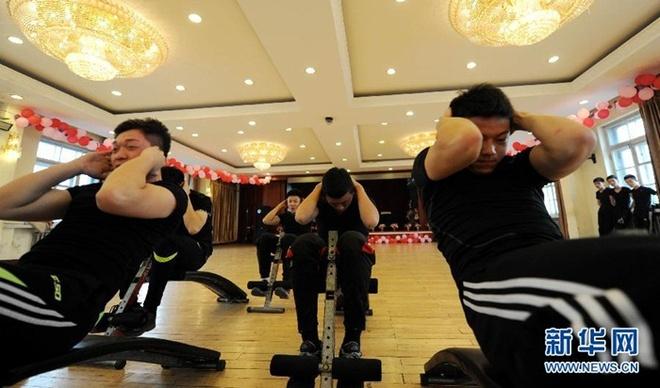 Ben trong lo luyen tiep vien hang khong Trung Quoc hinh anh 7 Các nam sinh luyện tập để có một thể hình cân đối.