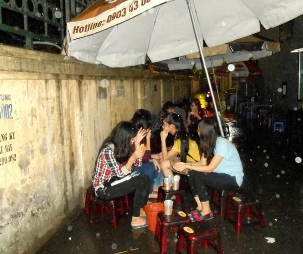 Bất chấp mưa gió, nhiều thực khách vẫn tìm đến quán ăn vỉa hè của Đức, co cụm dưới những chiếc ô để thưởng thức món thịt xiên nướng.