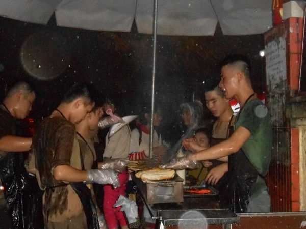Đức và nhân viên hối hả làm việc dưới trời mưa để phục vụ lượng khách đông đảo. Ngoài những người ngồi ăn tại chỗ, rất nhiều người vẫn đợi mua để mang đi.
