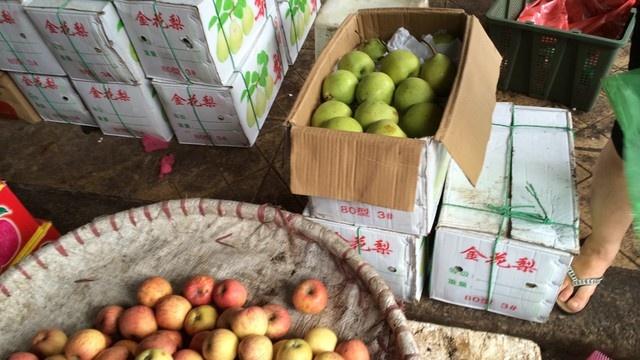 """Le, tao, thanh long: Ra khoi thung la thanh hang mien Nam hinh anh 2 Chủ các sạp hàng thản nhiên lấy táo, lê từ các thùng Trung Quốc ở phía sau và bán cho khách hàng với """"danh"""" hoa quả miền Nam."""
