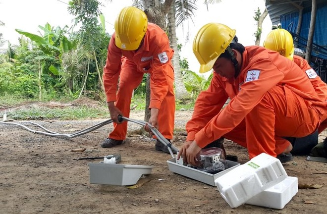Nhân viên điện lực lắp đặt hệ thống điện cho hộ gia đình ở xã Trung Hiếu, huyện Vũng Liêm, Vĩnh Long.