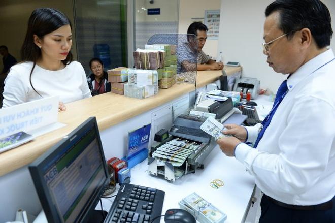 Gui USD, co lai cung nhu khong hinh anh 1 Theo các chuyên gia, việc hạ lãi suất tiền gửi USD sẽ khuyến khích doanh nghiệp, người dân chuyển qua nắm giữ VND. Trong ảnh: Người dân giao dịch USD tại NH ACB chiều 28-9.
