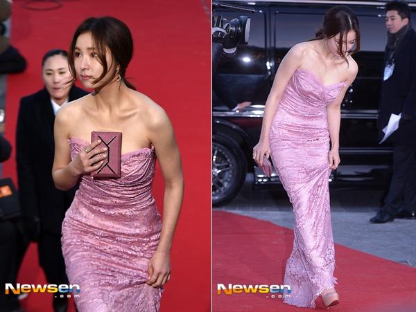 Shin Se Kyung cẩn thận bước đi vì sợ dẫm phải vạt váy, cô còn cầm ví che vòng 1 gợi cảm.