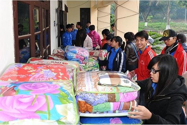 Thanh niên tình nguyện Đại học Kinh tế Quốc dân phân phát chăn cho các đối tượng chính sách.