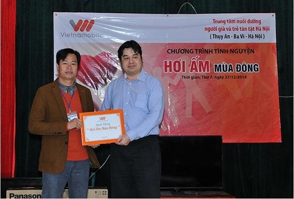 Đại diện Công ty viễn thông Vietnamobile trao quà cho Trung tâm nuôi dưỡng người già và trẻ em tàn tật Hà Nội.