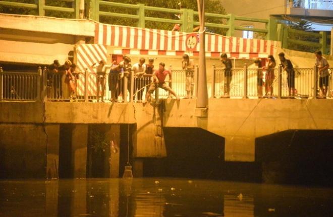 Cach nao bao ve ca kenh Nhieu Loc? hinh anh 4 15 người tập trung quan sát một người câu được con cá trê to.