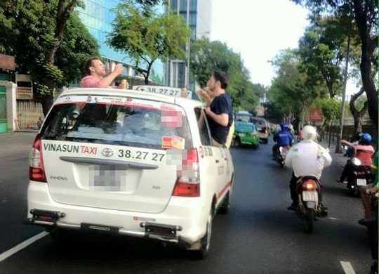 3 ong Tay nhau tren noc taxi gay nao dong duong pho Sai Gon hinh anh 1 Hình ảnh 3 vị khách nước ngoài ngồi cửa taxi thò đầu ra trên nóc để nhậu khiến nhiều người bất bình.