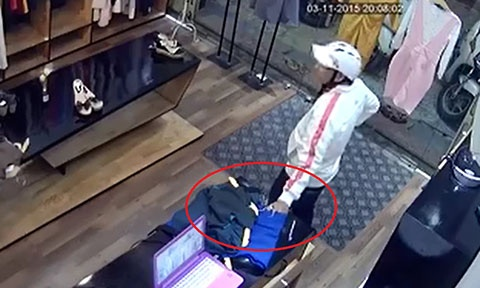 Clip thanh nien vo mua vay cho ban gai de trom dien thoai hinh anh 3 Lợi dụng chủ shop không để ý, nam thanh niên đưa tay kéo điện thoại ra ngoài.