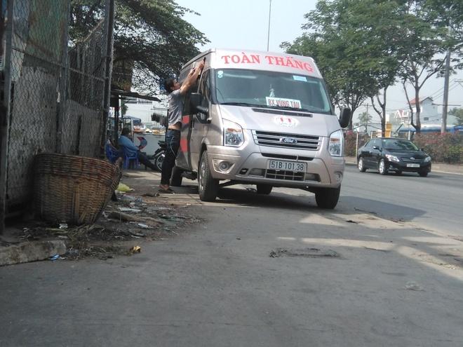 Vua mao xe thuong hieu vua rut tuyp sat doa danh khach hinh anh 1 Một nhân viên đang 'phù phép' xe mình thành xe thương hiệu Toàn Thắng trên quốc lộ 1 đoạn quận Thủ Đức, TP HCM sáng 26/12.