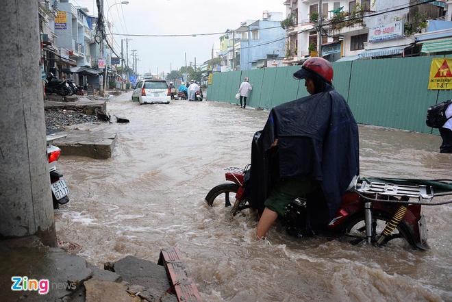 Be trai suyt ngat xiu khi di tren con duong ngap nuoc hinh anh 2 Nước ngập sâu nên một số người đi xe máy đã chạy vào hẻm để kiếm lối ra.