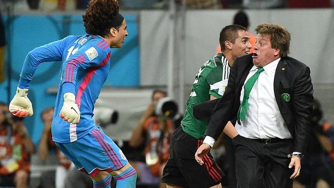 goalkeeper Guillermo Ochoa (L) and Mexico's coach Miguel Herrera (R) celebrate a goal by their team during a Group A football match between Croatia and Mexico at the Pernambuco Arena in Recife.