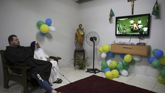 A priest from the Franciscan order and a nun from the enclosed monastery of Imaculada Conceicao watch on television as Brazil's Neymar grimaces as he is carried off the pitch after being injured in the 2014 World Cup quarter-final.