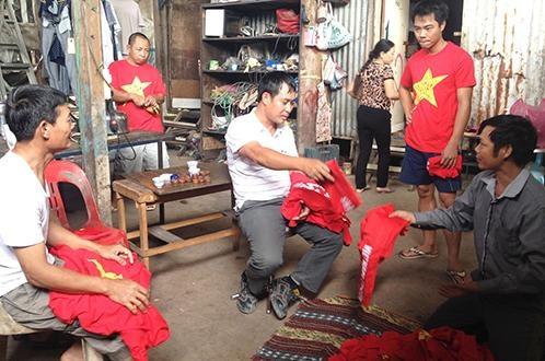 Nhung CDV dac biet cua tuyen U19 Viet Nam hinh anh 1 Ông Cao Xuân Dưỡng (bìa phải) phát áo cờ đỏ sao vàng cho các CĐV khi đi cổ vũ U19 VN trong trận đấu với U19 Thái Lan. Ảnh: N.K.
