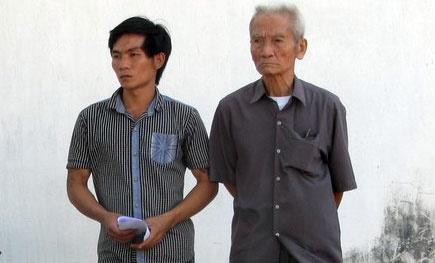 Ông Truyện (bên phải) và con của bị can Huỳnh Văn Nén lặng người khi nhận thư trả lời không chấp nhận cho tại ngoại của cơ quan điều tra.