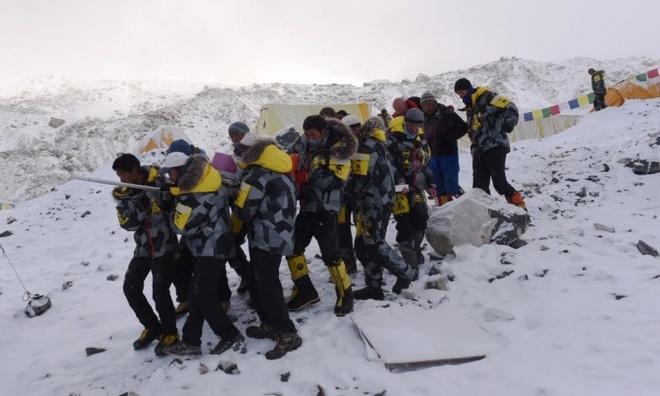 Hien truong tuyet lo o Everest hoang tan nhu sau tran bom hinh anh 3 Những người leo núi giúp vận chuyển nạn nhân bị thương đến trực thăng cứu hộ. Ảnh: AFP