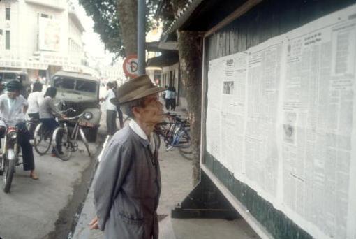 Viet Nam nhung nam dau thong nhat qua anh quoc te hinh anh 2 Một cụ già đọc các bản tin trên tờ báo dán tại một góc phố ở Hà Nội. Tác giả bộ ảnh, nhà báo Halstead, từng là trưởng văn phòng đại diện của hãng tin UPI tại Sài Gòn để đưa tin về chiến ở Việt Nam.