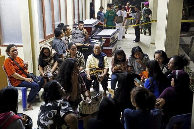 Thân nhân người bị nạn ngồi chờ đợi tin tức người nhà bên ngoài bệnh viện Adam Malik. Ảnh: Reuters