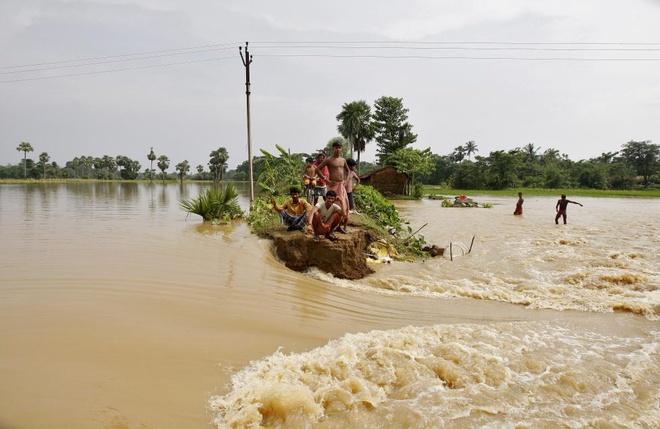 Anh bao lu o chau A an tuong nhat tuan qua (2/8 - 9/8) hinh anh 1 Người dân quận Howrah, bang West Bengal, Ấn Độ, mắc kẹt giữa dòng nước lũ ngày 5/8 và đang đợi đội cứu hộ tới đưa họ đến nơi an toàn. Ít nhất 75 người chết và hàng chục người Ấn Độ phải sống tạm trong những trại khẩn cấp do tình trạng ngập lụt nghiêm trọng. Ảnh: Reuters