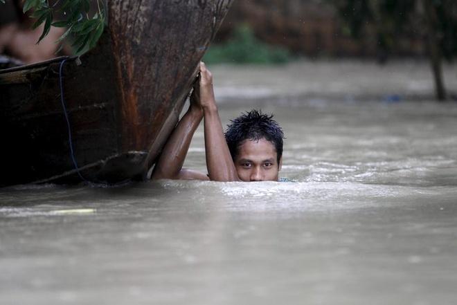 Anh bao lu o chau A an tuong nhat tuan qua (2/8 - 9/8) hinh anh 2 Một thanh niên ở thị trấn Zalun, đồng bằng Irrawaddy tại Myanmar phải dùng thuyền để di chuyển do nước lũ dâng cao. Tổng thống Thein Sein thúc giục người dân tránh các vùng trũng và nên tìm đến các khu đất cao hơn để lánh nạn. Ảnh: Reuters