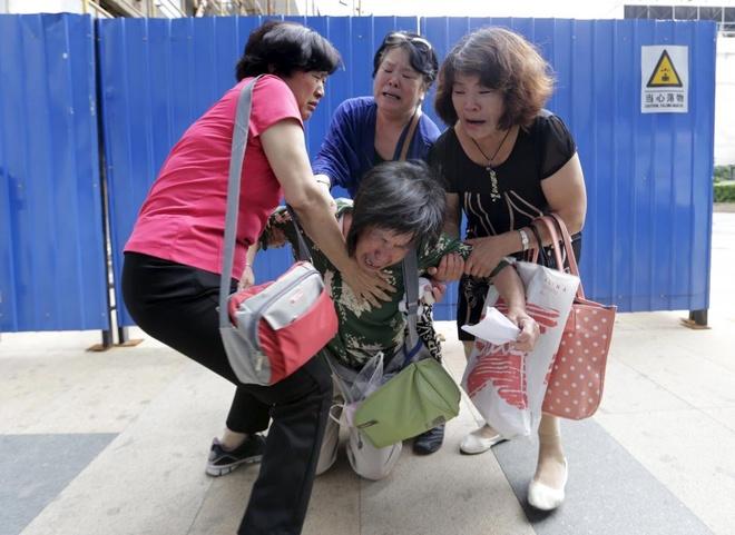 Anh bao lu o chau A an tuong nhat tuan qua (2/8 - 9/8) hinh anh 4 Bà Bao Lanfang, thân nhân của một gia đình là hành khách trên chuyến bay MH370, biểu tình trước đại sứ quán Malaysia ở Bắc Kinh ngày 6/8. Họ yêu cầu chính phủ Malaysia và hãng Malaysia phải cung cấp thông tin chính xác, sau khi nhà chức trách Pháp tuyên bố tìm thấy vật thể nghi là mảnh vỡ của máy bay mất tích. Kuala Lumpur đã khẳng định mảnh kim loại chính là của MH370 nhưng Paris chưa đưa ra kết luận tương tự. Ảnh: Reuters