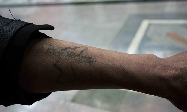 Một hướng dẫn viên người Triều Tiên khoe hình xăm trên cánh tay với dòng chữ Reunification (thống nhất) và hình minh họa về bản đồ bán đảo Triều Tiên. Ảnh: Guardian