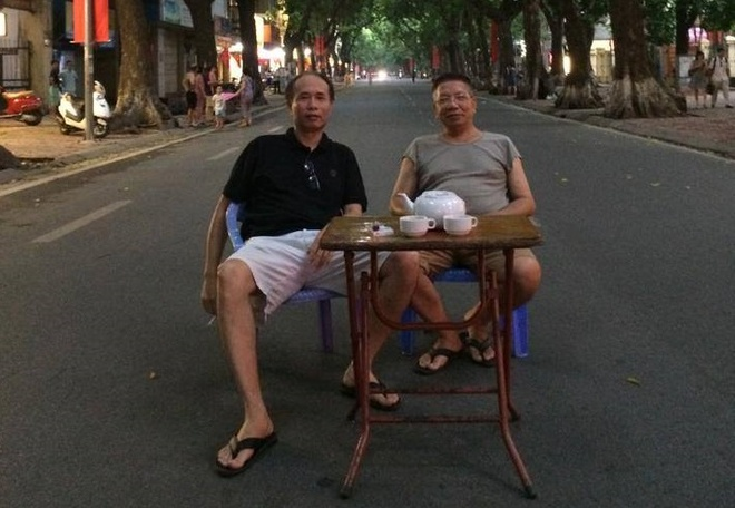 Hai nguoi dan ong ngoi giua duong pho Ha Noi uong tra hinh anh