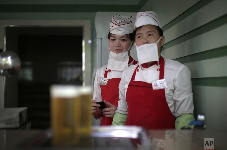 Kim Yon Hui (trái) và Yang Pok Yong (phải) chờ phục vụ khách hàng tại cửa hàng bia Taedonggang ở Bình Nhưỡng. Ảnh chụp ngày 7 tháng 5 năm 2016.