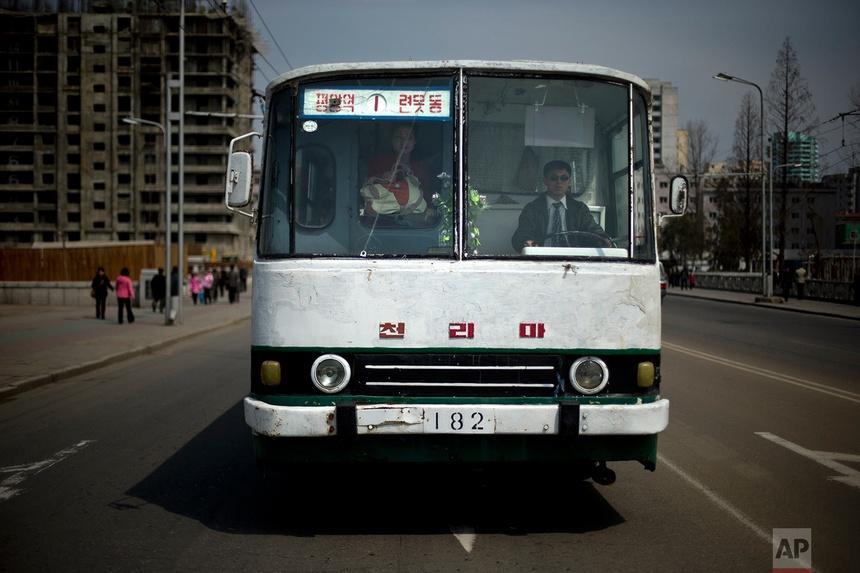 Tài xếxe buýt và người phụ nữ nhìn qua kính chắn gió bị nứt ở Bình Nhưỡng ngày 15 tháng 4 năm 2013.