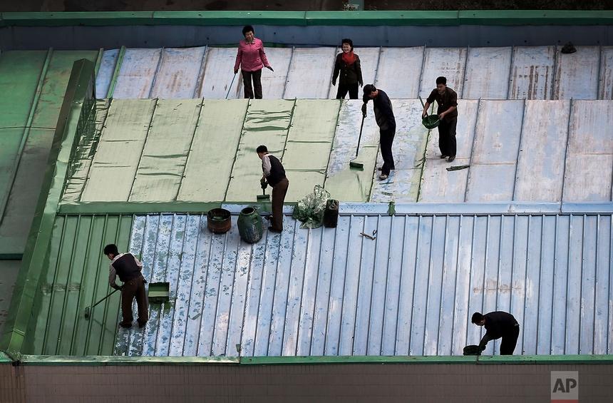 Các công nhân đang sơn lại mái của một nhà hàng ở trung tâm thành phố Bình Nhưỡng ngày cuối tháng 10/2014.