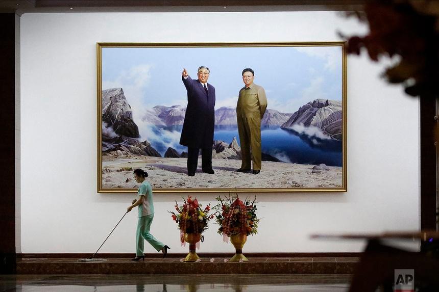 Một nhân viên quét sàn trong sảnh khách sạn trước bức ảnh có chân dung của cố lãnh đạo Triều Tiên Kim Il Sung, trái, và Kim Jong Il vào ngày 19 tháng 6 năm 2017, tại Bình Nhưỡng.