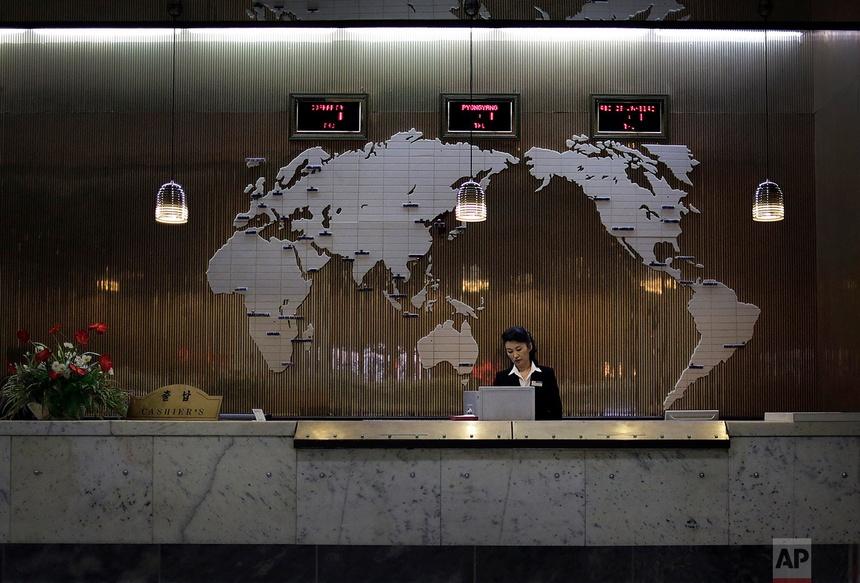 Một nhân viên khách sạn đứng tại bàn tiếp tân được trang trí bản đồ thế giới vào ngày 23 tháng 10 năm 2014, tại Bình Nhưỡng.