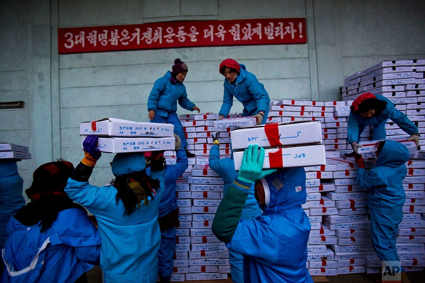 Công nhân nhà máy hải sản sunchaeo Bong Corp ở Rajin, thuộc đặc khu kinh tế Rason, đang vận chuyển các hộp hải sản ra một chiếc xe tải của Trung Quốc.