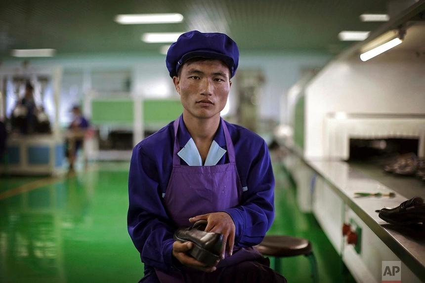 Kang Jong Jin, một cựu quân nhân 28 tuổi, làm công việc gắn đế giày tại một nhà máy giày ở Wonsan, Triều Tiên. Ảnh chụp ngày 22 tháng 6 năm 2016.